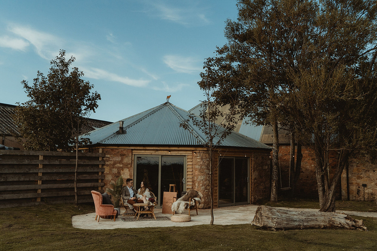 Outdoor seating area with wicker and mismatched furniture at The Cow Shed