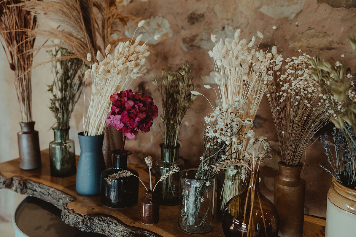 Dried flowers in vases on oil drums with wood tabletop Small Wedding Scotland Inspo