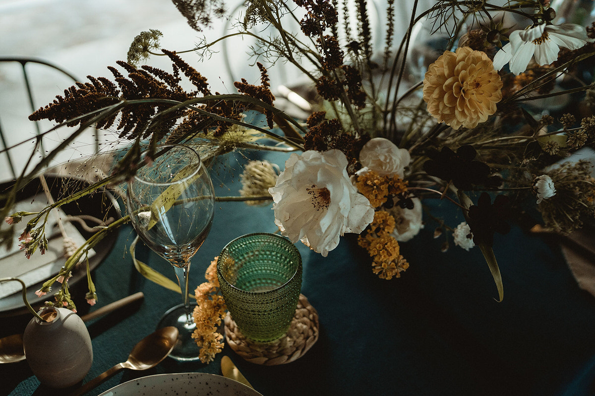 Autumnal and wild wedding table flower styling on blue tablecloth