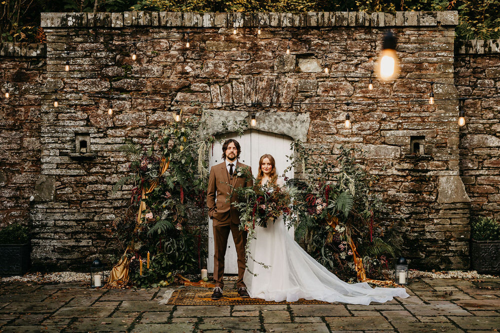 Rich colour outdoor floral installation and large wild wedding bouquet