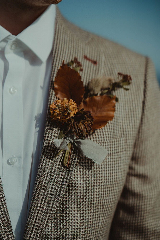 Wild autumnal buttonhole for seaside clifftop elopement on the East Coast of Scotland