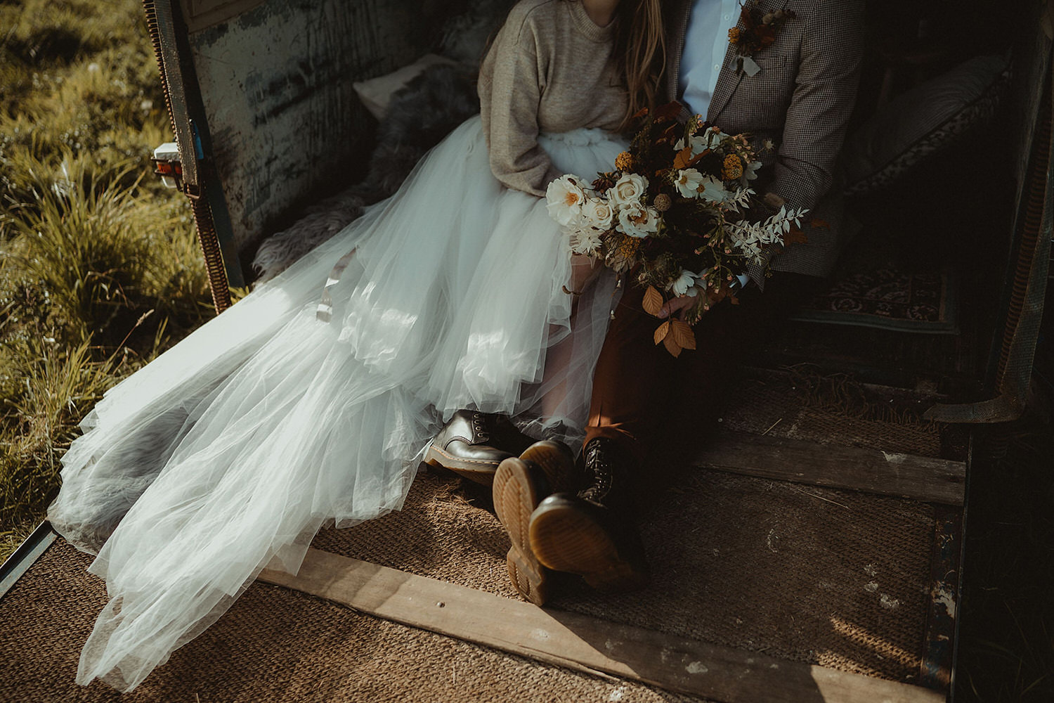 Wedding horsebox seating area for elopement by the sea with wild autumnal wedding bouquet and buttonhole